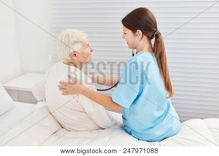 Nurse with stethoscope is examining a sick elderly woman