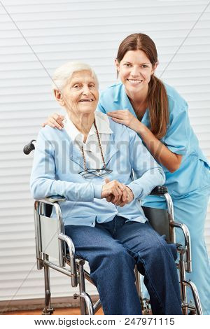 Happy elderly woman in wheelchair with a young nurse or caregiver
