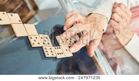 Old hands of seniors lay playing pieces while playing dominoes in retirement home