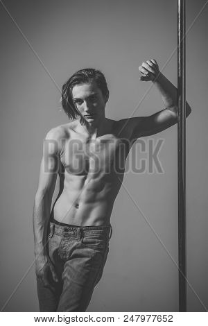 Erotic Services. Shirtless Man Pole Dancing On A Grey Background. Young Strong Pole Dance Man With N