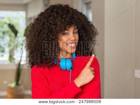 African american woman wearing headphones cheerful with a smile of face pointing with hand and finger up to the side with happy and natural expression on face looking at the camera.