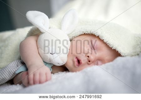 Newborn baby boy portrait on white carpet closeup. Motherhood and new life concept