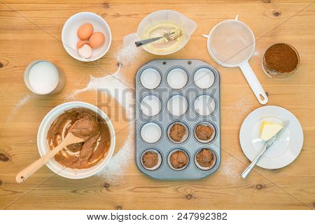 Overhead flat lay arrangement of Cup Cake making mixture and equipment on a kitchen table.