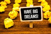 Handwriting text writing Have Big Dreams Motivational Call. Concept meaning Future Ambition Desire Motivation Goal White text black paint wooden board clip desk yellow paper notes warning poster