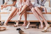 Cropped picture of attractive fashion girls 20s wearing dresses choosing and trying on summer stilettos during bridal shower in hotel room poster
