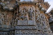 Sculpture of dancing Shiva on the centre left and Vishnu on the right, west side walls, Hoysaleshwara temple, Halebidu, Karnataka, India. view from West. poster