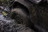 Offroad. Wheel with little cloud of smoke, defocused. Fragfment of car stuck in dirt, close up. Dirty offroad tire covered with mud. Crossover overcomes obstacles in forest area. Impassibility of roads concept poster