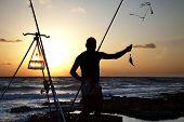 Fisherman silhouette catching a fish. Horizontal shot poster