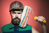 Painter man. Room painting job. Handsome bearded worker with paint roller. Professional painter, decorator, builder worker, repairman, tradesman, handyman with paint roller. Repair, building concept. poster