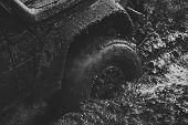 Competition of off-road cars. Fragfment of car stuck in dirt, close up. Dirty offroad tire covered with mud. Wheel with cloud of smoke, defocused. Crossover overcomes obstacles in forest area. Extreme entertainment concept. poster