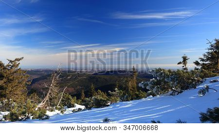 View On Hilly Snowless Forests From Snowy Mountain On A Sunny Day