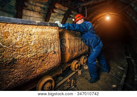 A Miner In A Coal Mine Stands Near A Trolley. Copy Space.