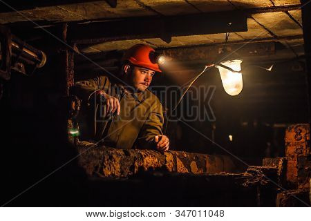 A Tired Miner In A Coal Mine Looks At The Light. Work In A Coal Mine. Portrait Of A Miner. Copy Spac