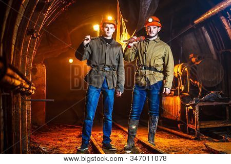 Miners In The Process Of Working With Tools In Their Hands. Coal Mine. Two Miners In The Mine. Copy
