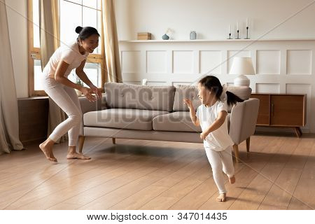 Overjoyed Ethnic Mother And Daughter Running Playing At Home