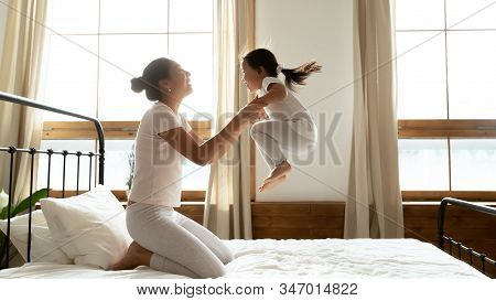 Overjoyed Young Mum And Little Daughter Play At Home