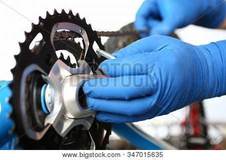Close-up Of Hands Of Male Master In Protective Blue Gloves. Skilled Craftsman Repairing Bicycle With