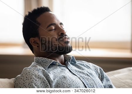 Tranquil Young African Man Resting Eyes Closed Breathing On Couch