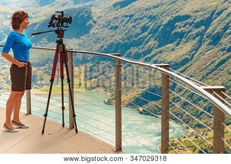 Female Tourist With Camera On Tripod Taking Travel Picture, Enjoying Mountains Landscape From Ornesv
