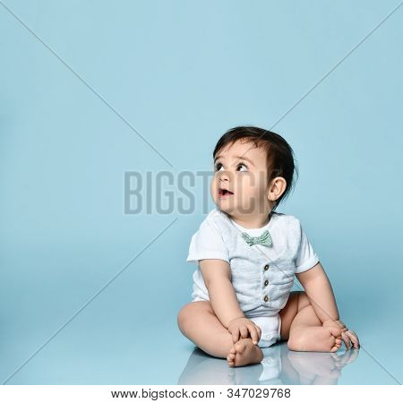 Toddler In White Bodysuit As A Vest With Bow-tie, Barefoot. He Is Sitting On The Floor Against Blue