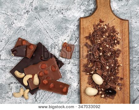 Broken Chocolate Bars, Chocolate Shavings And Chocolate Covered Nuts On Gray Stone Background. Top V