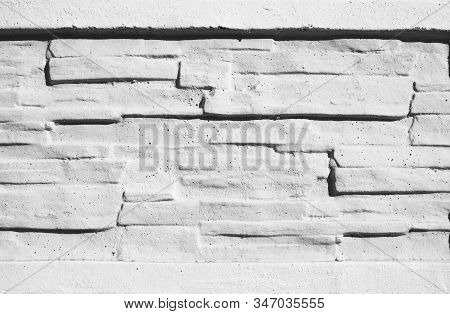 Texture stained blocks of stonework. Plastered facade of building of modern blocks tiles. Grey fence of facing stone. White brick wall. poster