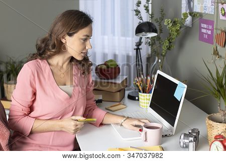 Young Woman Shopping Online With Credit Card And Laptop Pc At Home