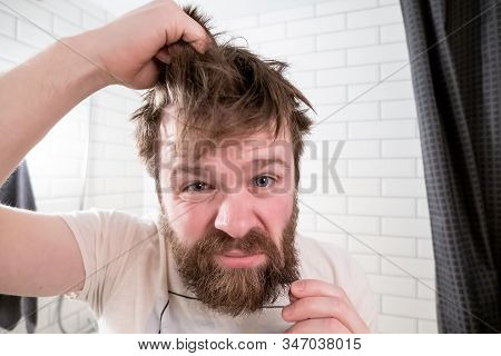 Overgrown Man, With A Shaggy Hairstyle And Beard, Looks In His Reflection In The Mirror And Is Dissa