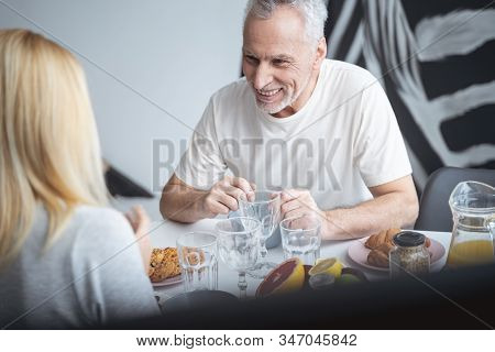 Mirthful Man Laughing At The Table Stock Photo