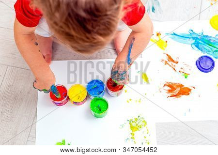Baby Drawing  Multi-colored Finger Paints. Baby Hands. Flat Lay. Artwork