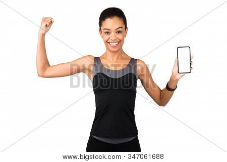 African American Girl In Fitwear Showing Phone Blank Screen And Biceps Recommending Fitness Applicat