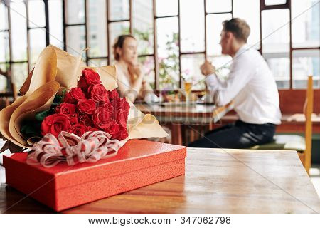 Horizontal Shot Of Beautiful Red Roses And Box Of Chocolate Lying On Cafe Table, Couple Dating On Ba