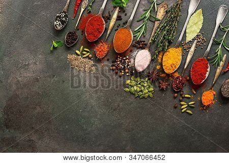 A Variety Of Spices, Herbs, Seeds In A Spoon On A Dark Painted Rustic Background. Assorted Colored D