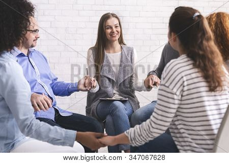 Group Therapy Session. Addicted People Holding Hands, Sitting In Circle Of Trust At Meeting In Rehab