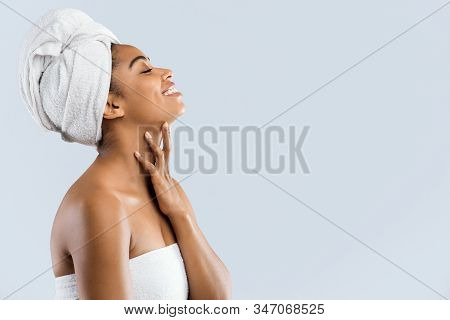 Side View Of Joyful Young African Woman Wrapped In White Bath Towels After Shower, Enjoying Her Silk
