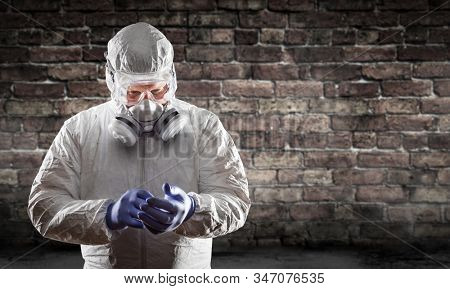 Man Wearing Hazmat Suit, Protective Gas Mask and Goggles Against Brick Wall.