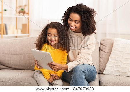 Cute Black Family Of Mother And Daughter Using Tablet Computer Watching Cartoons Together Sitting On