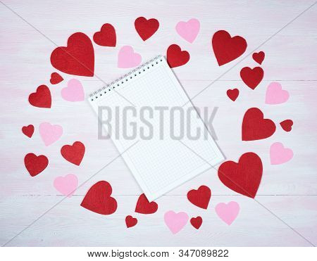 Top View Of A Notebook Surrounded By Hearts On A Lilac Wooden Background. Valentines Day Concept