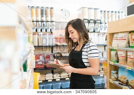 Female Owner Checking Inventory Of Food Products In Grocery Store