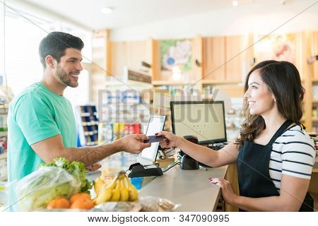Smiling Female Cashier With Buyer At Checkout Counter In Grocery Store