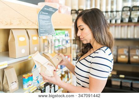 Confused Mid Adult Woman Choosing Food Product In Grocery Store
