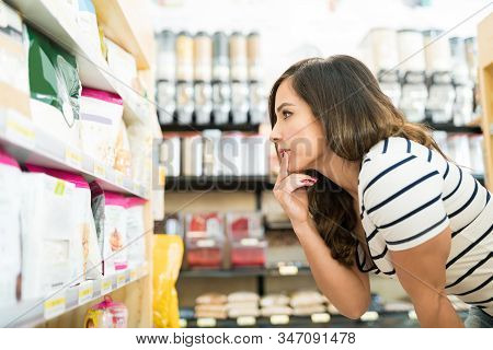 Confused Mid Adult Woman Choosing Food Products On Shelf In Grocery Store