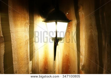 Glowing Street Lamp On The Background Of A Wooden Fence At Night. Light Permeates The Darkness. Stre