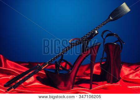 Adult Sex Games. Kinky Lifestyle. Spank And A Pair Of Black High-heeled Shoes On The Red Linen Near