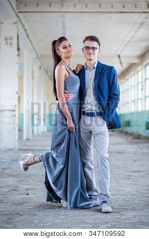 Prom Couple. Handsome Guy In Blue Suit And Beautiful Girl In Glamorous Silver Blue Dress, Ready For
