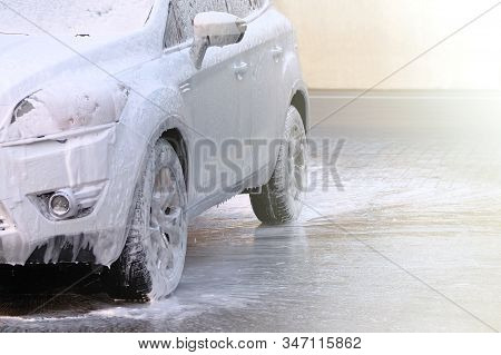 Soaping With Foam On Car In Self-service Car Wash. White Car At Car Wash Station. Water And White So