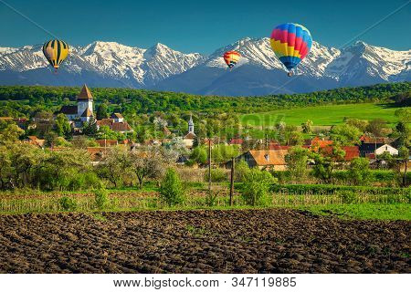 Leisure And Travel Concept With Hot Air Balloons Over The Rural Village. Spring Landscape With Flowe