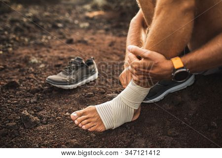 Man Bandaging Injured Ankle. Injury Leg While Running Outdoors. First Aid For Sprained Ligament Or T