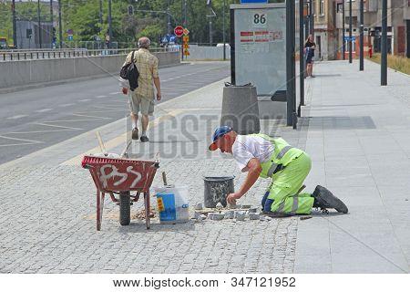 Lodz / Poland. 18 July 2019:  Laying Paving Slabs By Mosaic. Road Paving. Man Making Repairing Of Si