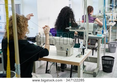 Young Dressmaker Women Sew Clothes On Sewing Machine In Tailor Shop